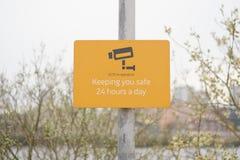 Zeichen CCTV in Kraft 24 Stunden pro Tag, das Sie orange minimales des sicheren Sicherheitswegweisers hält Lizenzfreies Stockfoto