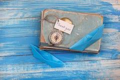 Zeichen danken Ihnen und Kompass auf altem Buch - Weinleseart Stockbilder