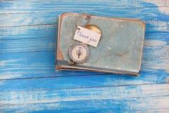 Zeichen danken Ihnen und Kompass auf altem Buch - Weinleseart Stockfotos