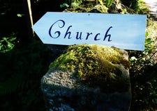 Zeichen, das in Richtung zu einer moosigen Wand der Kirche zeigt stockfotos