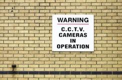 Zeichen der Überwachungskamera in Kraft auf Backsteinmauer lizenzfreies stockfoto