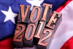 Zeichen der ABSTIMMUNG 2012 auf amerikanischer Flagge Stockbild