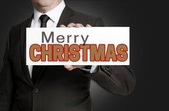 Zeichen der frohen Weihnachten gehalten durch Geschäftsmannkonzept Stockbilder