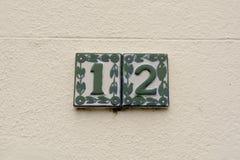 Zeichen der Hausnummer 12 auf Wand - in den Keramikfliesen Stockfotografie
