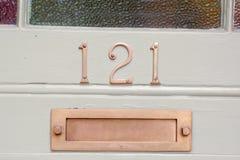 Zeichen der Hausnummer 121 und Briefkasten auf Tür Lizenzfreies Stockfoto