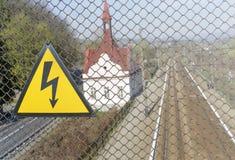 Zeichen der Hochspannung auf dem Hintergrund der Eisenbahn Stockbild