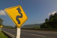 Zeichen der kurvenreichen Straße auf blauem Himmel Stockfotografie
