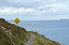 Zeichen der unebenen Fahrbahn auf Rocky Mountain Walking Track durch die Seeküste in Ben von Howth, Irland Stockbilder