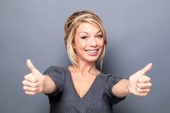 Zeichen des doppelten Sieges für aufgeregte Frau mit dem modischen blonden Haar Lizenzfreie Stockfotografie
