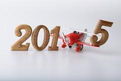 Zeichen des neuen Jahres 2015 gemacht durch hölzernes Zahl- und Spielzeugflugzeug Stockbild