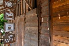 Zeichen, die vor einem alten hölzernen Hauptaufenthalt hängen stockbilder