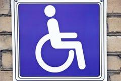 Zeichen eines Mannes in einem Rollstuhl Stockfotos