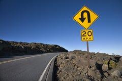 Zeichen entlang einer Kurve auf einer Straße. stockbild