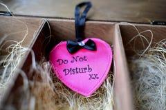 Zeichen in Form eines rosa Herzens mit der Aufschrift stören nicht in einer Holzkiste mit Stroh lizenzfreie stockfotografie
