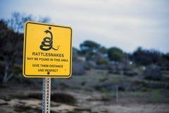 Zeichen mit einer Warnung für Klapperschlangen Lizenzfreie Stockbilder