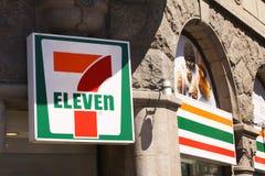 7 Zeichen mit elf Logos auf einer Wand 7-Eleven ist eine internationale Kette von Mini-Märkten, die hauptsächlich als Vorrecht fu stockfotografie