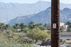 Zeichen mit Symbol der Gefahr auf einer hölzernen Säule lizenzfreie stockfotos