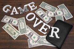 Zeichen-Spiel über Dollar und leerer Geldbeutel auf hölzernem Hintergrund Stockbild