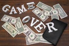 Zeichen-Spiel über Dollar und leerer Geldbeutel auf hölzernem Hintergrund Lizenzfreie Stockbilder