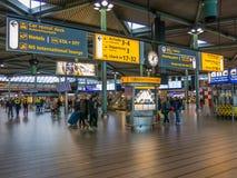 Zeichen und Leute an Flughafen Schiphol Amsterdam Lizenzfreie Stockbilder