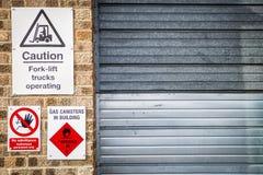 Zeichen und Mitteilung der Aufmerksamkeit und der Gefahr, die an einer Wand h?ngen lizenzfreie stockbilder