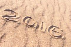 Zeichen 2016 und Sonne geschrieben auf sandigen Strand Sommerreisekonzept Lizenzfreie Stockfotos
