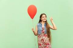 Zeichen V! Der schöne blonde Jugendliche mit roten Ballons auf einem grünen Hintergrund Lizenzfreie Stockfotos