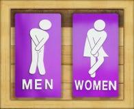 Zeichen weiblich und männliches Badezimmer auf hölzernem Hintergrund Lizenzfreies Stockbild