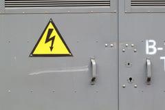 Zeichenaufmerksamkeitshochspannung auf der Metalltür stockfotografie