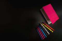 Zeichenstifte mit einem rosa Notizbuch auf einem schwarzen Hintergrund Lizenzfreie Stockfotos