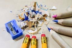 Zeichenstifte und Bleistiftspitzer auf einem hölzernen Bürotisch Zeichnet w Stockbilder