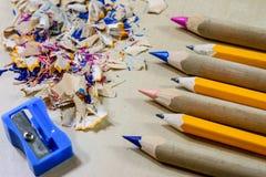 Zeichenstifte und Bleistiftspitzer auf einem hölzernen Bürotisch Zeichnet w Stockfotografie
