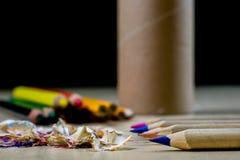 Zeichenstifte und Bleistiftspitzer auf einem hölzernen Bürotisch Zeichnet w Lizenzfreie Stockfotografie