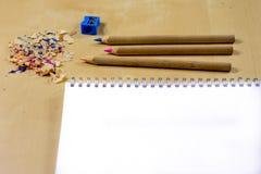 Zeichenstifte und Bleistiftspitzer auf einem hölzernen Bürotisch Zeichnet w Lizenzfreie Stockbilder