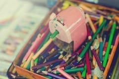 Zeichenstifte und Bleistiftspitzer im Kasten lizenzfreies stockfoto