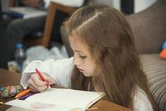 Zeichnen des kleinen Mädchens bunte Bilder unter Verwendung der Bleistiftzeichenstifte Stockbilder
