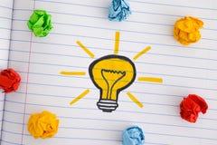 Zeichnen einer Glühlampe und der bunten zerknitterten Papierbälle stockfoto