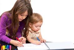Zeichnen mit zwei Mädchen Stockbild