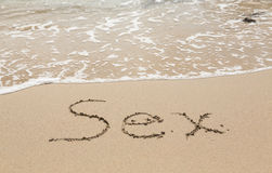 Zeichnen in Sand durch Ozean des Sexwortes Lizenzfreie Stockfotos