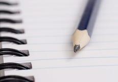 Zeichnen Sie auf Notizbuch an Stockfoto