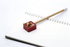 Zeichnen Sie auf weißen Notizbuch-, Bleistiftspitzer- und Bleistiftschnitzeln an Lizenzfreie Stockfotografie