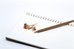 Zeichnen Sie auf weißen Notizbuch-, Bleistiftspitzer- und Bleistiftschnitzeln an Stockfotografie