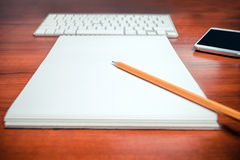 Zeichnen Sie das Lügen auf einem Notizblock mit Tastatur und Handy auf einem Hintergrund an Flache Schärfentiefe Lizenzfreies Stockfoto