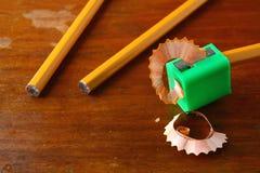 Zeichnen Sie in einem Bleistiftspitzer und in zwei unsharpened Bleistiften an Stockfotografie
