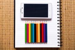 Zeichnen Sie Farbe und Mobiltelefon auf Notizbuch, Draufsicht an Stockfoto