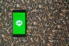Zeichnen Sie Logo auf Smartphone auf Hintergrund von kleinen Steinen Stockfoto
