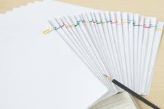 Zeichnen Sie mit Notizbuch und bunter Papierklammer mit Schreibarbeit und Berichten an Stockfoto