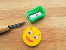 Zeichnen Sie Stift, Bleistiftführung und Radiergummi auf hölzernem Hintergrund an Stockbilder