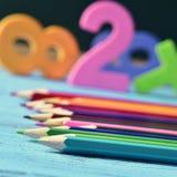 Zeichnen Sie Zeichenstifte und Zahlen auf einem blauen Holztisch an Lizenzfreies Stockfoto