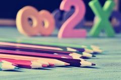 Zeichnen Sie Zeichenstifte und Zahlen auf einem blauen Holztisch an, gefiltert Stockfoto